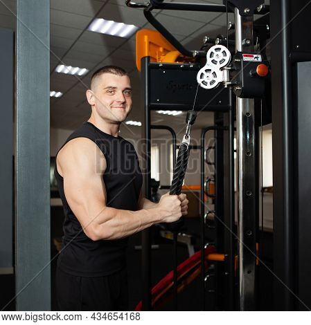 A Young Handsome Coach In A Black Uniform Against Background Of A Simulator In Gym. Muscular Athleti