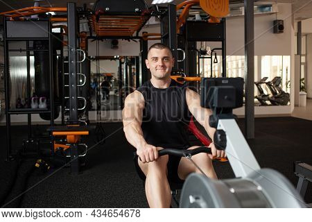A Handsome Male Coach Sits On A Simulator In Gym. Imitation Rowing, Boat With Oars, For Rowers. Smil