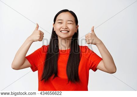Beautiful Brunette Asian Girl Shows Her Suppport, Winks And Shows Thumbs Up In Approval, Like Someth