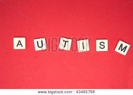 Autism spelled out in plastic letter pieces on red background