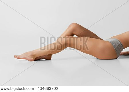 Beautiful Slender Female Hips And Legs Isolated On Gray Studio Background. Natural Beauty, Spa, Anti