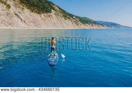 July 15, 2021. Anapa, Russia. Sporty Woman On Stand Up Paddle Board At Blue Sea. Surfer Woman Walkin