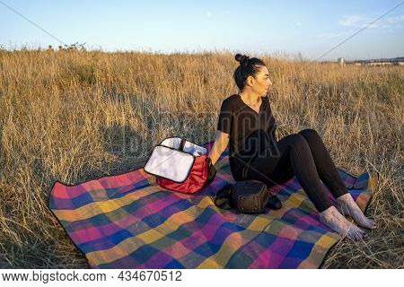 Beautiful Brunette Woman Sitting On Yellow Grass On Picnic Blanket With Basket