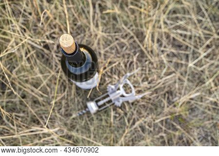 Open Bottle Of Red Wine With Empty Label, Natural Cork And Metal Corkscrew