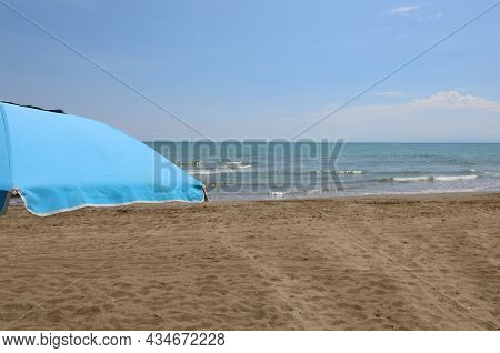 Isolated Blue Umbrella On The Beach Without People Symbol Of Relaxation And Summer Vacation