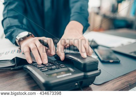 Businessman Dialing Desk Phone In The Office. Telephone Dialing ,contact And Customer Service.