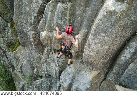 Young Man Climbing Steep Wall Of Rocky Mountain. Male Climber Overcomes Challenging Route. Engaging