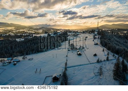 Aerial Winter Landscape With Small Village Houses Between Snow Covered Forest In Cold Mountains In T