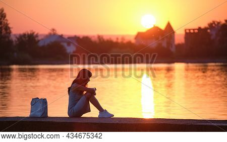 Lonely Young Woman Sitting Alone On Lake Shore Enjoying Warm Evening. Wellbeing And Relaxing In Natu
