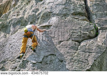 Strong Male Climber Climbing Steep Wall Of Rocky Mountain. Sportsman Overcoming Difficult Route. Eng