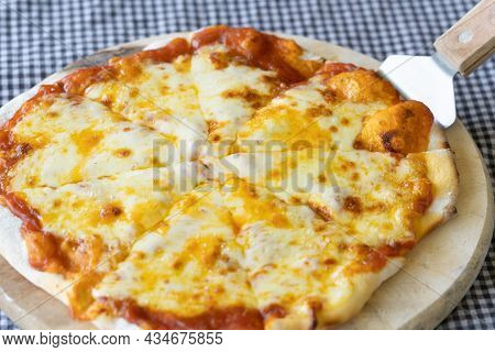 Homemade Pizza Made From Dough Topped With Spices Like Ham, Sausage , Vegetables And Cheese