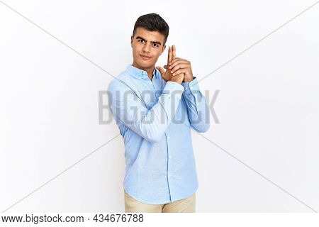 Young hispanic man wearing business shirt standing over isolated background holding symbolic gun with hand gesture, playing killing shooting weapons, angry face