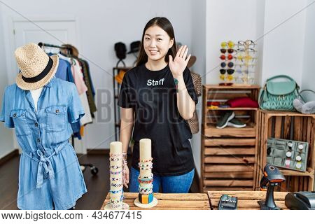 Young asian woman working as manager at retail boutique waiving saying hello happy and smiling, friendly welcome gesture