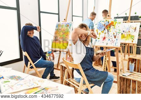 Group of middle age artist at art studio smiling cheerful playing peek a boo with hands showing face. surprised and exited