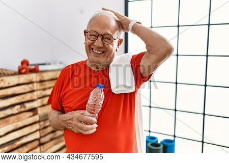 Senior man wearing sportswear and towel at the gym confuse and wondering about question. uncertain with doubt, thinking with hand on head. pensive concept.