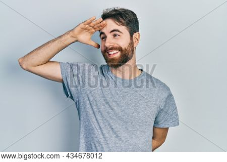Caucasian man with beard wearing casual grey t shirt very happy and smiling looking far away with hand over head. searching concept.