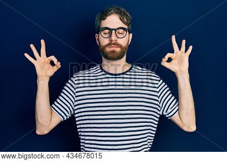 Caucasian man with beard wearing striped t shirt and glasses relax and smiling with eyes closed doing meditation gesture with fingers. yoga concept.