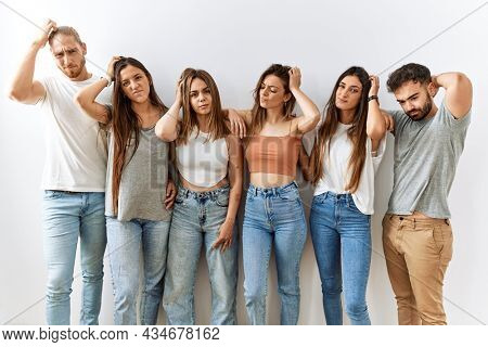 Group of young friends standing together over isolated background confuse and wondering about question. uncertain with doubt, thinking with hand on head. pensive concept.