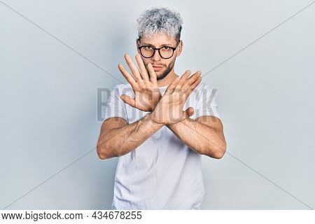 Young hispanic man with modern dyed hair wearing white t shirt and glasses rejection expression crossing arms doing negative sign, angry face