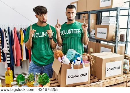 Young gay couple wearing volunteer t shirt at donations stand pointing up looking sad and upset, indicating direction with fingers, unhappy and depressed.