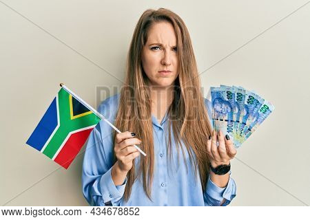 Young blonde woman holding south african flag and rands skeptic and nervous, frowning upset because of problem. negative person.