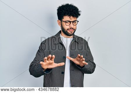 Young arab man with beard wearing glasses disgusted expression, displeased and fearful doing disgust face because aversion reaction. with hands raised