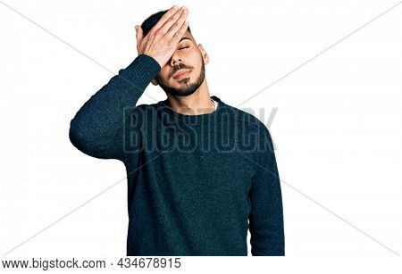 Young hispanic man with beard wearing casual winter sweater surprised with hand on head for mistake, remember error. forgot, bad memory concept.
