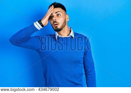 Young hispanic man with beard wearing casual blue sweater surprised with hand on head for mistake, remember error. forgot, bad memory concept.