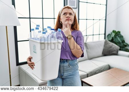 Young redhead woman holding recycling wastebasket with plastic bottles thinking concentrated about doubt with finger on chin and looking up wondering
