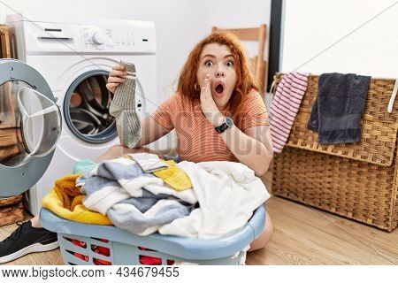 Young redhead woman putting dirty laundry into washing machine hand on mouth telling secret rumor, whispering malicious talk conversation
