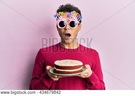 Handsome hispanic man wearing funny happy birthday glasses holding cake in shock face, looking skeptical and sarcastic, surprised with open mouth