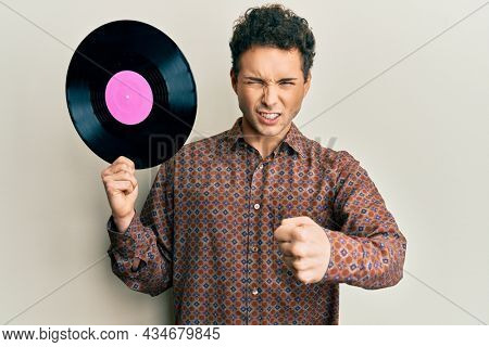 Young handsome man holding vinyl disc annoyed and frustrated shouting with anger, yelling crazy with anger and hand raised