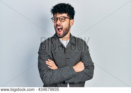 Young arab man with beard wearing glasses with arms crossed gesture angry and mad screaming frustrated and furious, shouting with anger. rage and aggressive concept.