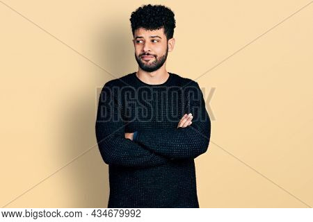 Young arab man with beard with arms crossed gesture smiling looking to the side and staring away thinking.