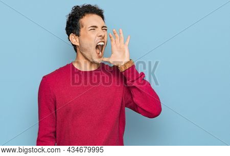 Young handsome man wearing casual clothes shouting and screaming loud to side with hand on mouth. communication concept.