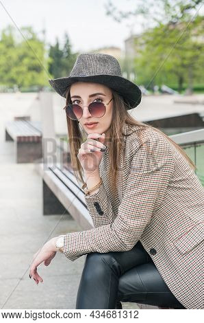 Beautiful Young Fashion Stylish Woman With Hat Sitting On The Bench