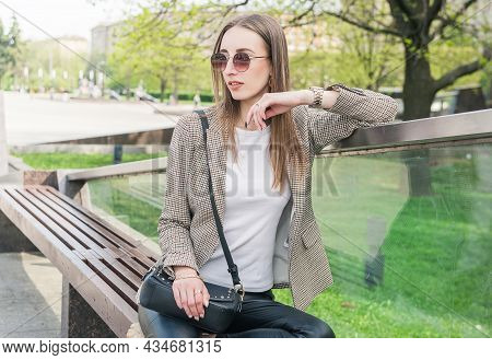 Beautiful Young Fashion Stylish Woman With Eyeglasses Sitting On The Bench
