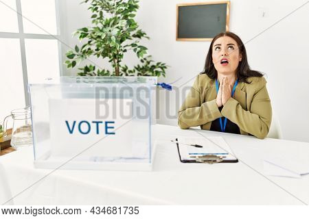 Young brunette woman sitting at election table with voting ballot begging and praying with hands together with hope expression on face very emotional and worried. begging.