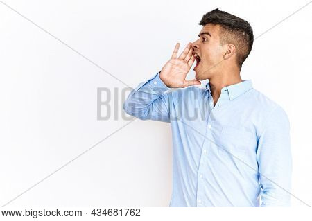 Young hispanic man wearing business shirt standing over isolated background shouting and screaming loud to side with hand on mouth. communication concept.