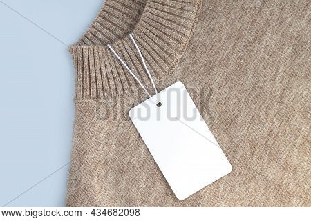 Mock-up Of Blank White Paper Price Tag Or Label On Warm Sweater Background Close-up