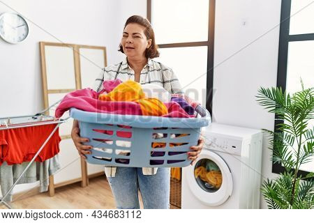 Middle age hispanic woman holding laundry basket winking looking at the camera with sexy expression, cheerful and happy face.