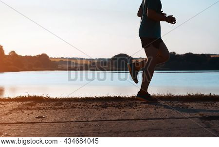 Young Man Doing Cardio Workout, Exercising And Running Early In The Morning At Dawn Near A Beautiful