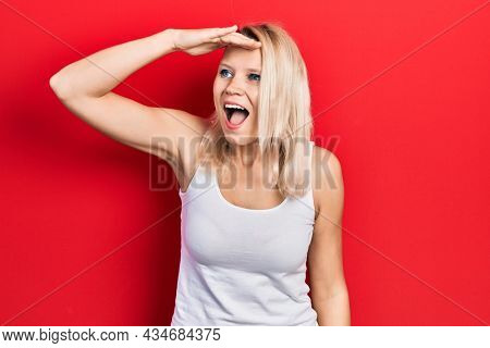 Beautiful caucasian blonde woman wearing casual white t shirt very happy and smiling looking far away with hand over head. searching concept.
