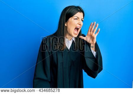Young hispanic woman wearing judge uniform shouting and screaming loud to side with hand on mouth. communication concept.