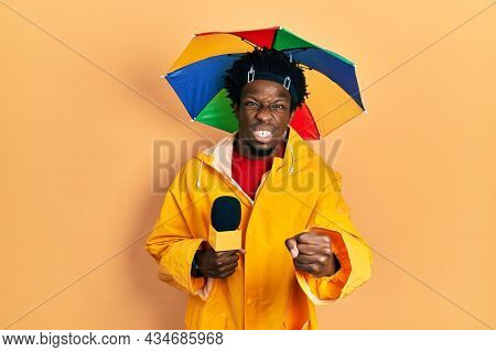 Young african american journalist man wearing yellow raincoat and umbrella cap annoyed and frustrated shouting with anger, yelling crazy with anger and hand raised