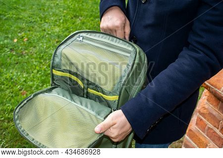 The Man Opens The Protective Pocket Of The Backpack. Organizer Panel For Various Accessories. Zipper