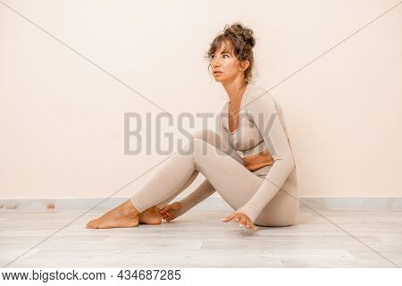 Young Woman With Long Hair, Fitness Instructor In Beige Sportswear, Preparing For Stretching And Pil