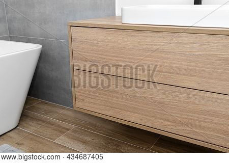A Modern Cabinet Hanging On The Washbasin In The Bathroom With A Matte Black Faucet, The Floor Is Co