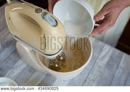 Step By Step The Process Of Making Sour Cream Pie Dough. Female Hands Add Milk To The Mixer Bowl For