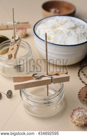 Glass Jars With Wicks And Clothespins As Stabilizers On Beige Background. Making Homemade Candles